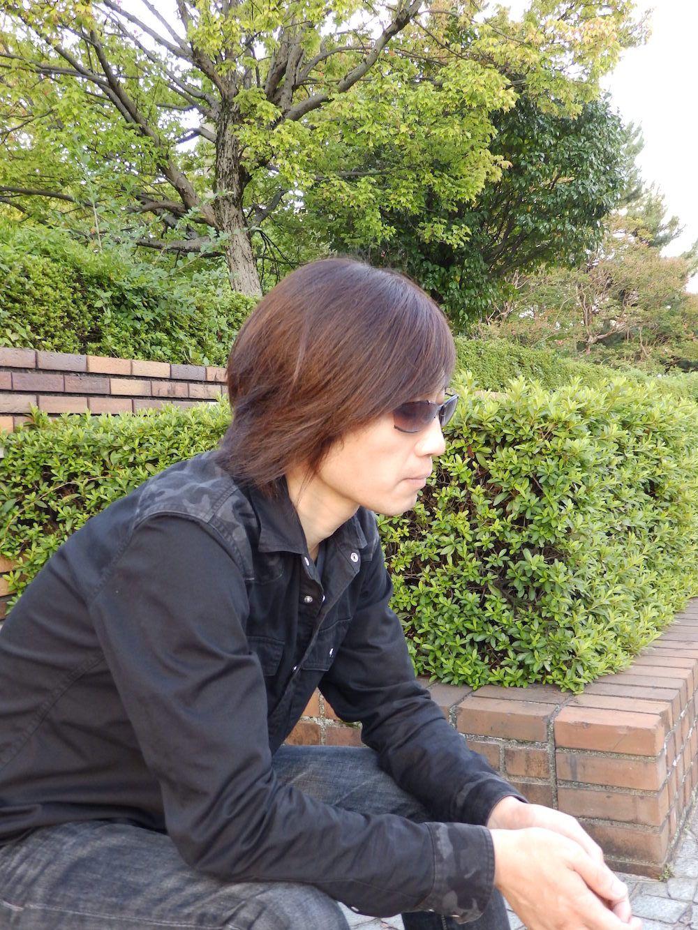 photo of Kazuma Kujo wearing sunglasses and sitting on a bench