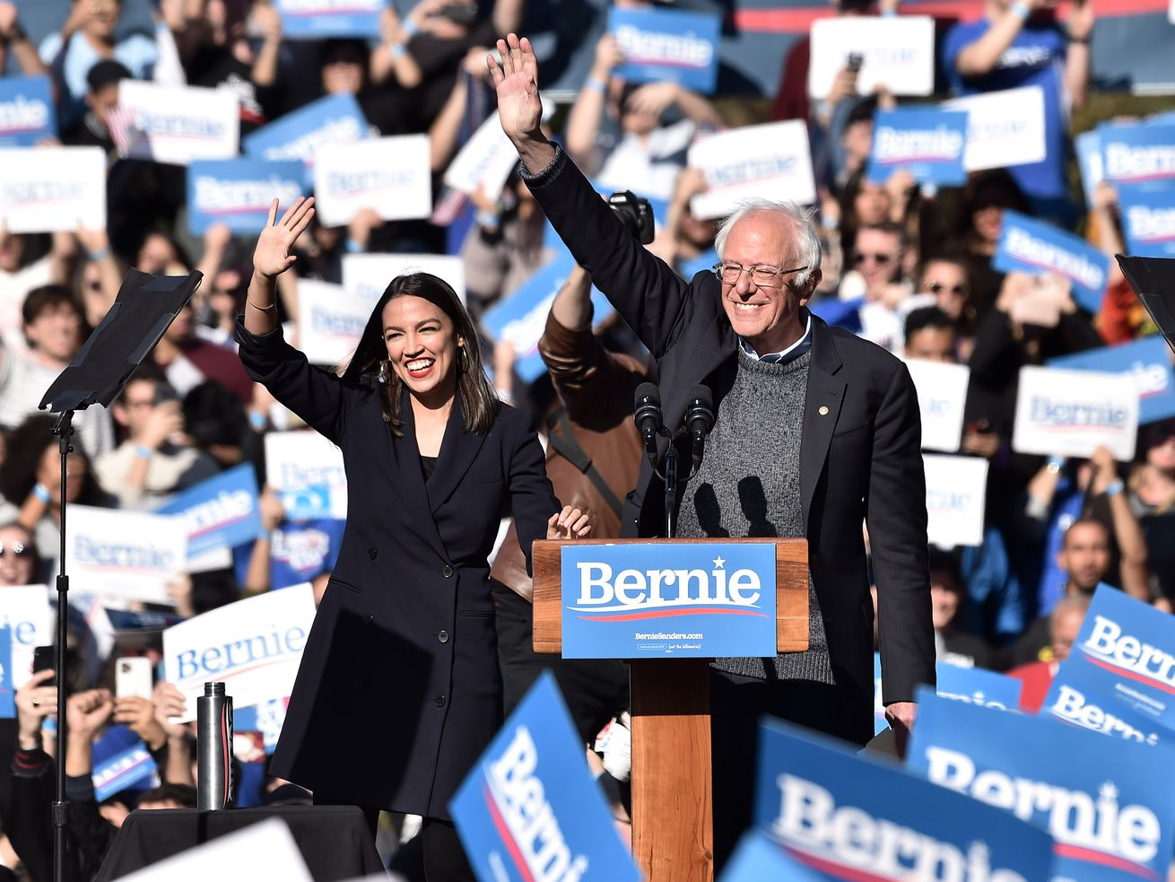 Sanders and AOC wave amid a sea of Bernie for president signs.
