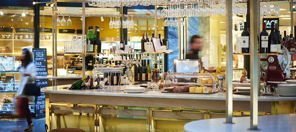 A bar decked out with brass and marble in a large, department-store like space
