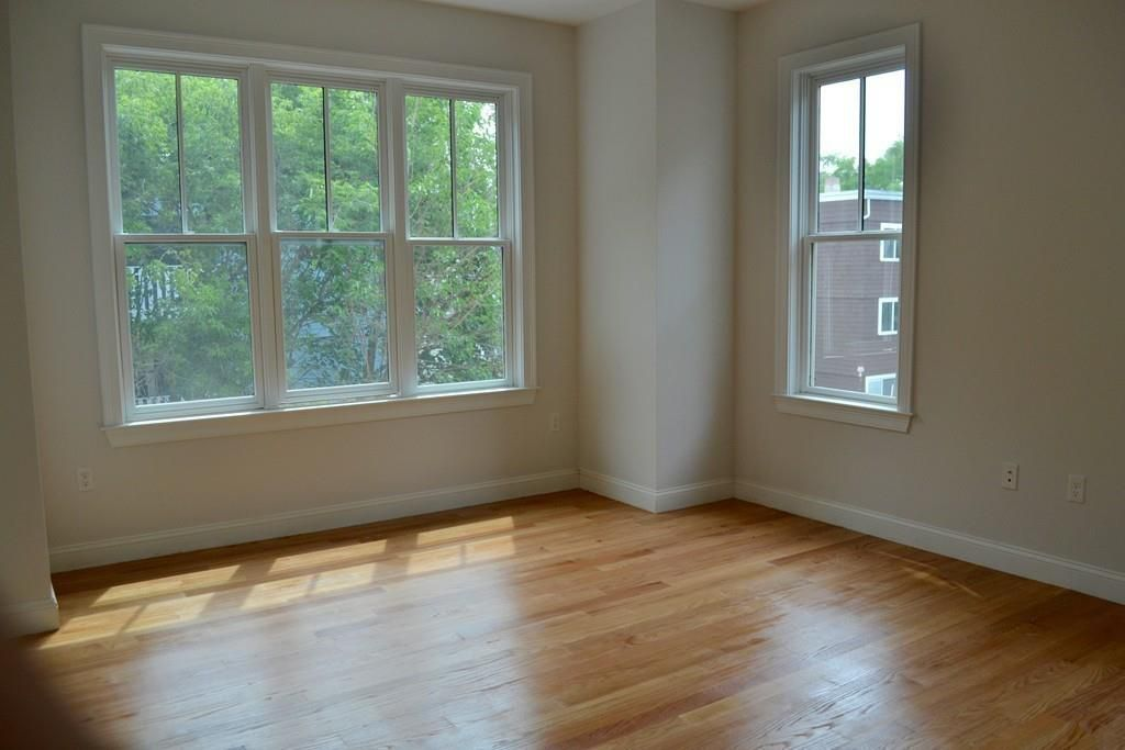 An empty bedroom with two sets of windows facing each other at a corner.