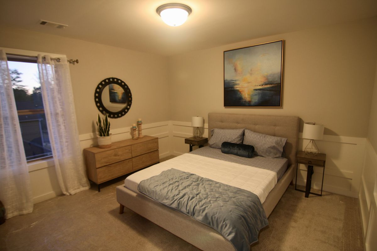 Inside the model unit's bedroom with white walls.