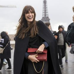 Caroline de Maigret looking oh so French in a chic black cape.