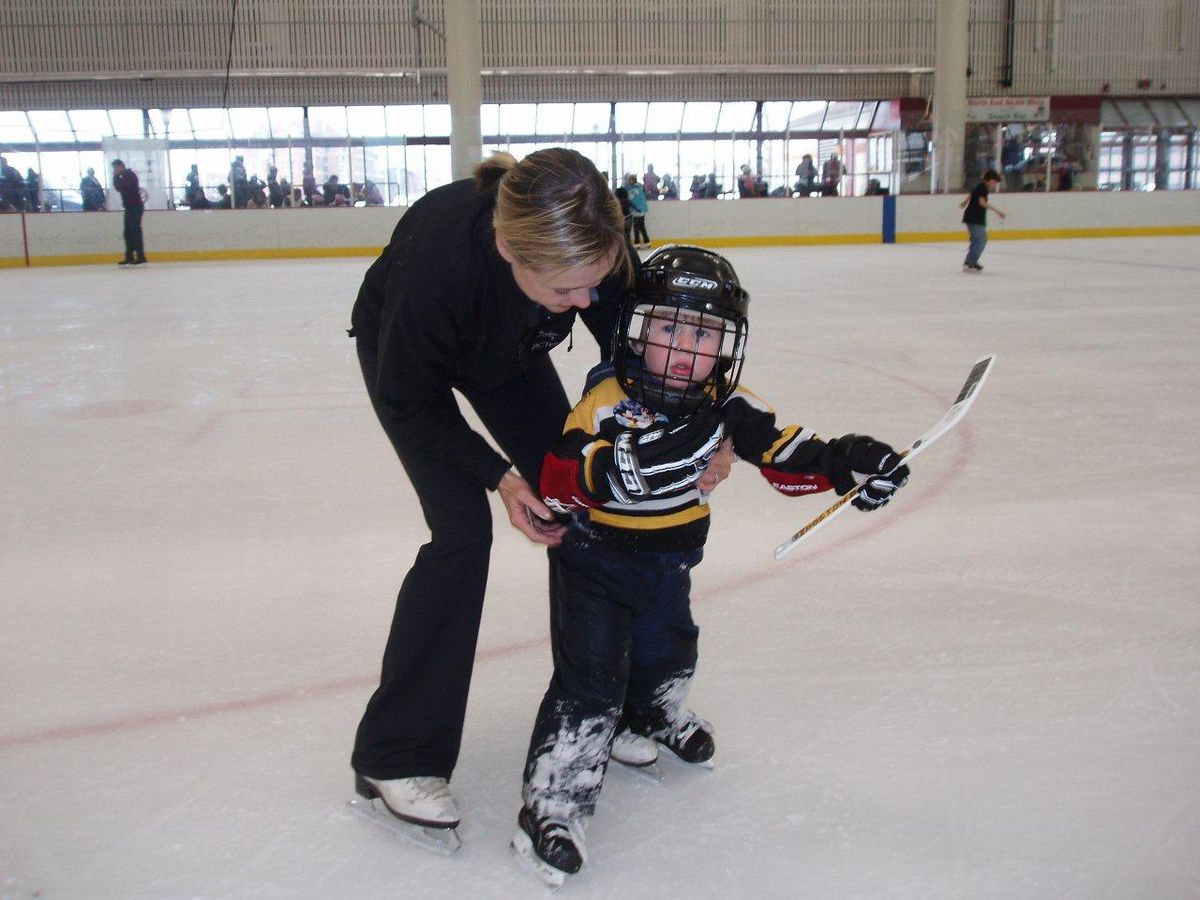A little kid with a hockey stick and in a hockey mask being helped by an adult on an ice-skating rink.