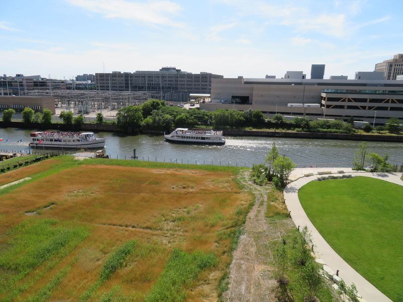 A high-level view of a natural prairie and a traditional lawn surrounded by a oval-shaped pathway. Two tour boats cross paths in the river beyond.
