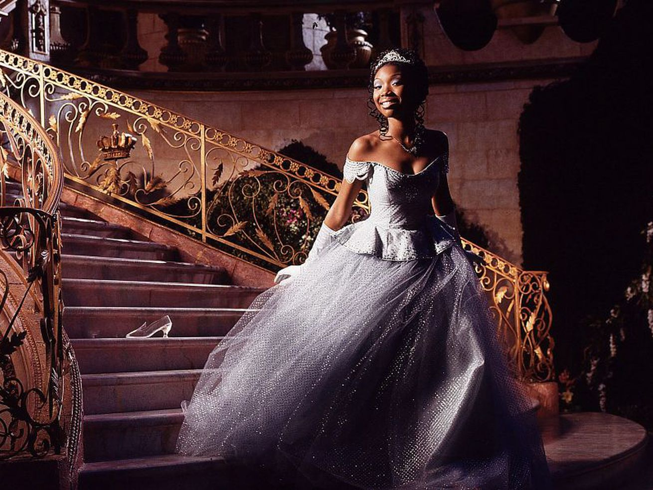 Brandy, dressed in a ballgown and tiara, steps down a sweeping staircase.