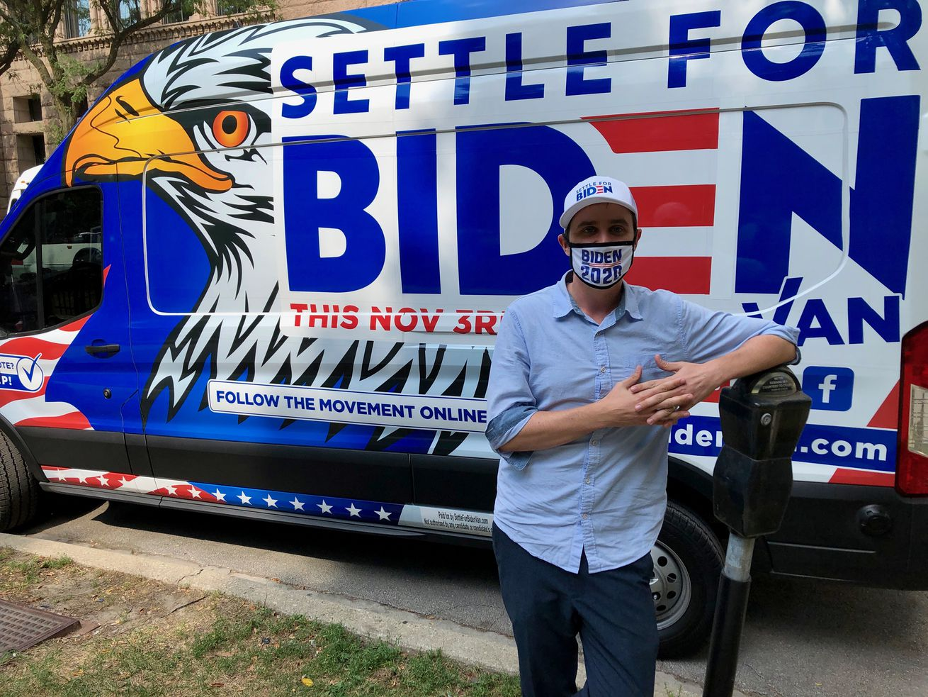 """A man in front of a red, white and blue van with """"Settle for Biden"""" and an eagle."""