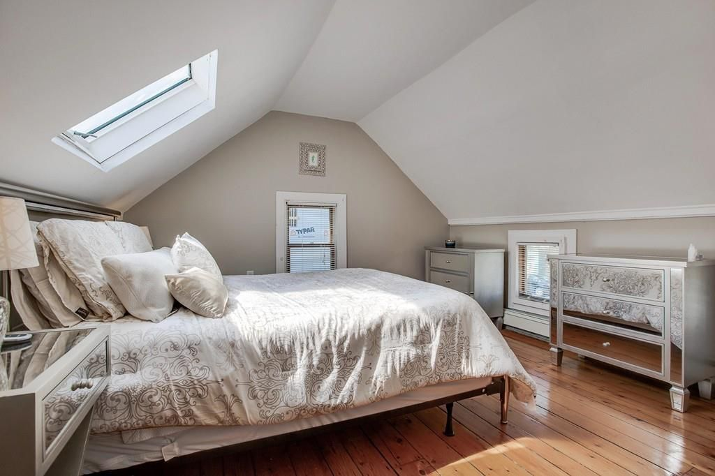 A bedroom with a bed beneath a skylight.