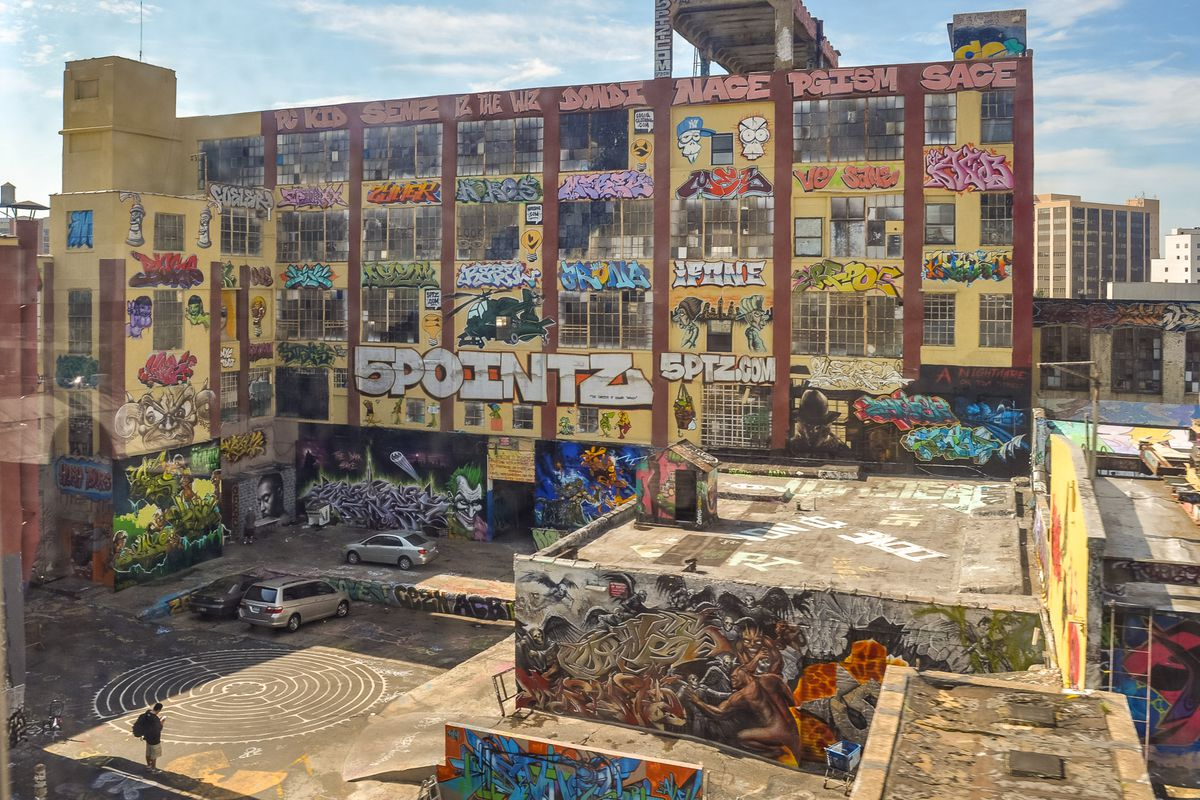 A  five-story industrial building covered in vibrant graffiti.