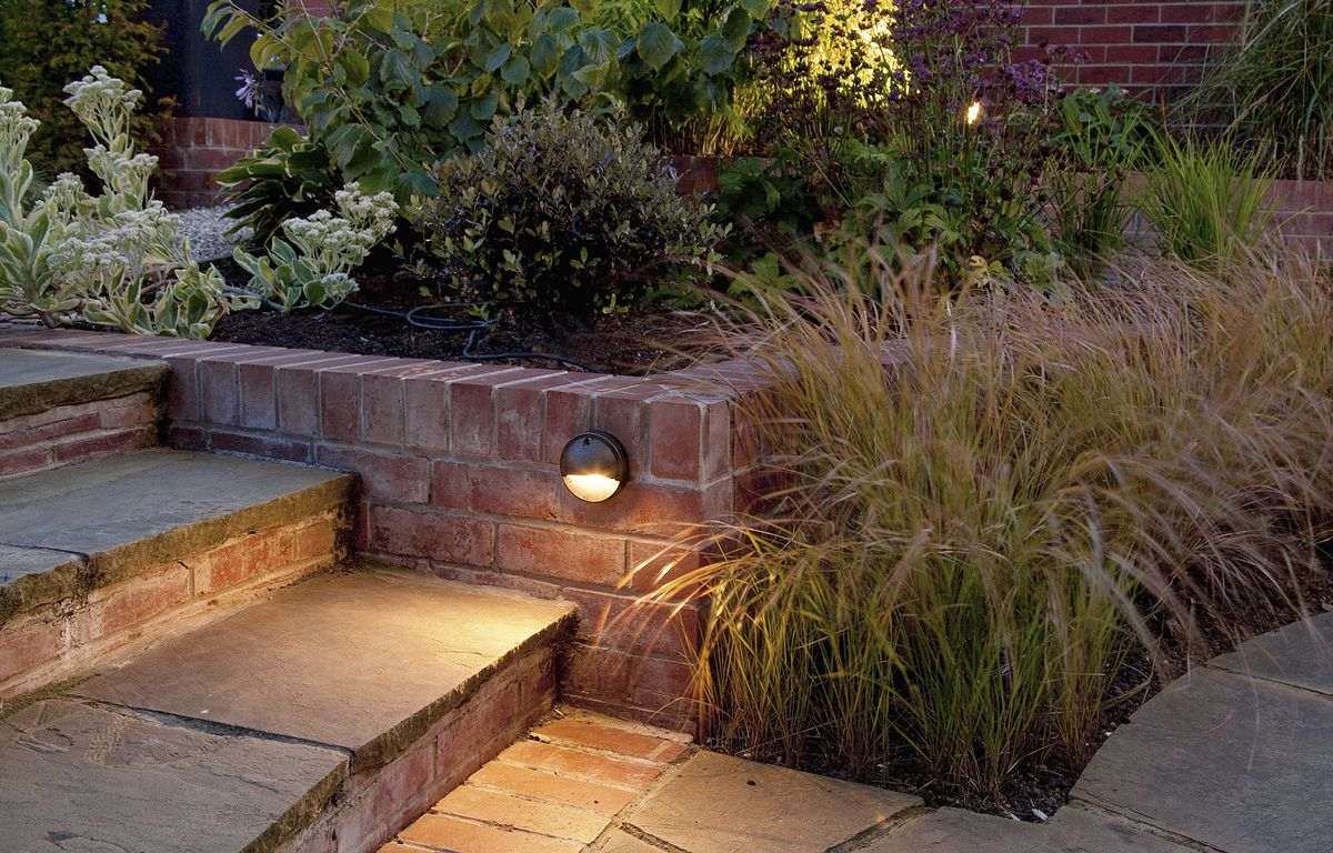 """<p>In this case, the lovely brickwork gets a glowing review from a well-placed light.</p> <p><strong>Similar to shown:</strong>Hinkley Hardy Island Hooded Step Light, about $65;<a href=""""http://lightology.com/"""" target=""""_blank"""">lightology.com</a></p> <script type=""""text/javascript""""> amzn_assoc_placement = """"adunit0""""; amzn_assoc_search_bar = """"true""""; amzn_assoc_tracking_id = """"hisldousent-20""""; amzn_assoc_ad_mode = """"manual""""; amzn_assoc_ad_type = """"smart""""; amzn_assoc_marketplace = """"amazon""""; amzn_assoc_r"""