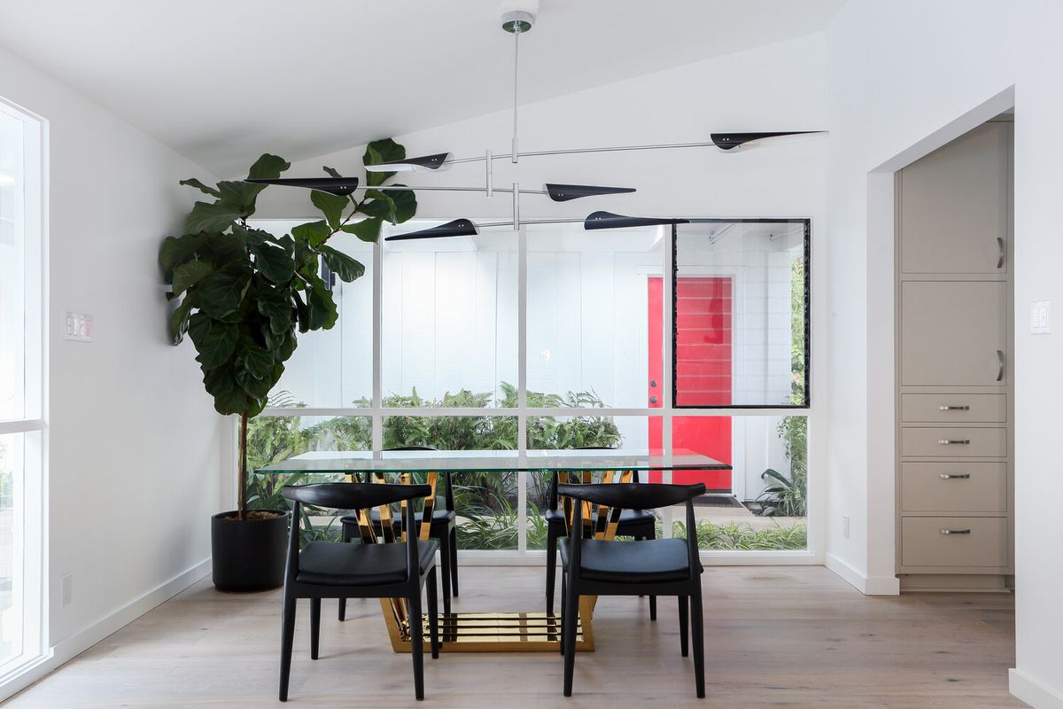 A photo of a dining table. In the background is a wall of windows.