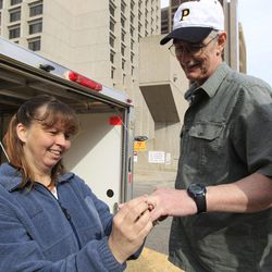 Tina Stone places the wedding band on husband David Stone's hand outside the federal building in Detroit, Friday, April 20, 2012. The FBI returned his possessions that were seized in March 2010. Stone was especially pleased to get his wedding ring back. Much of the returned gear is military-style vests and other accessories worn by members of the Hutaree militia when they trained in the woods of southern Michigan.