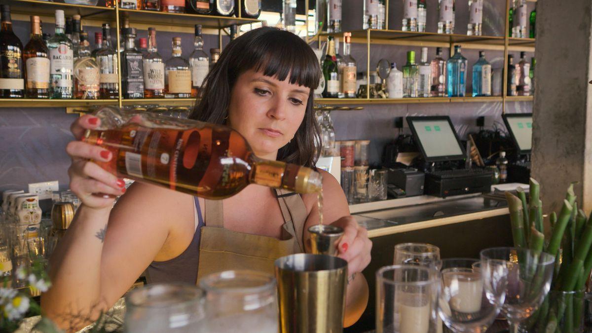 A woman mixes up a drink behind a bar.