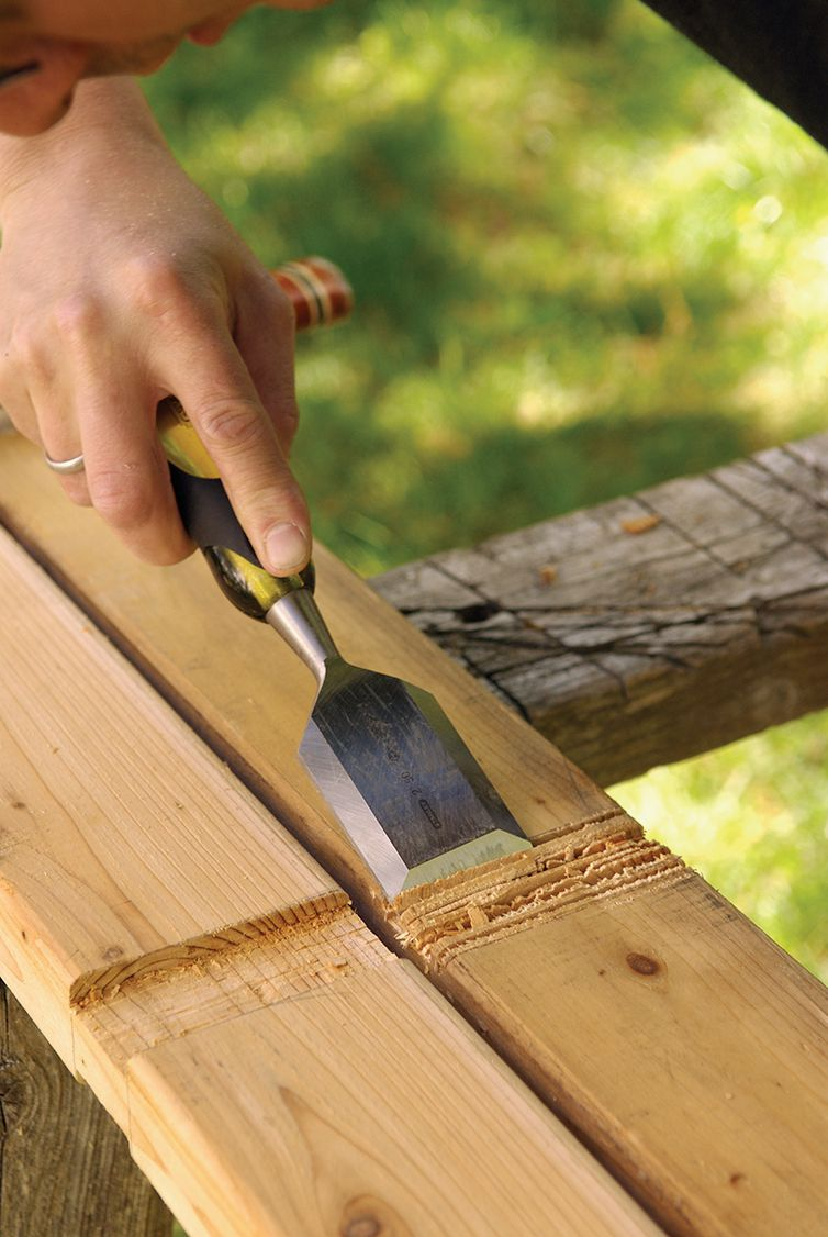 Man Uses Chisel To Smooth Notches On Trellis Wood Frame