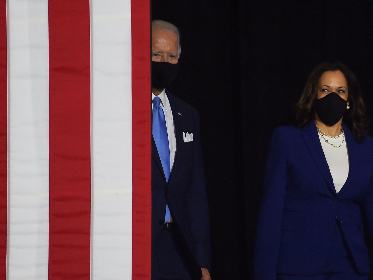 Joe Biden and Kamala Harris walking out from behind a flag-stripped banner.