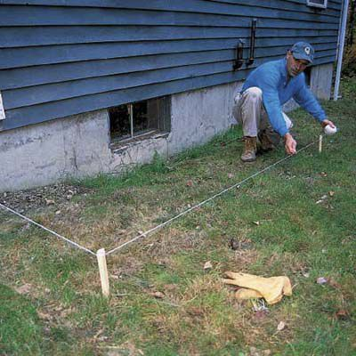 Laying out the trench for the downspout.