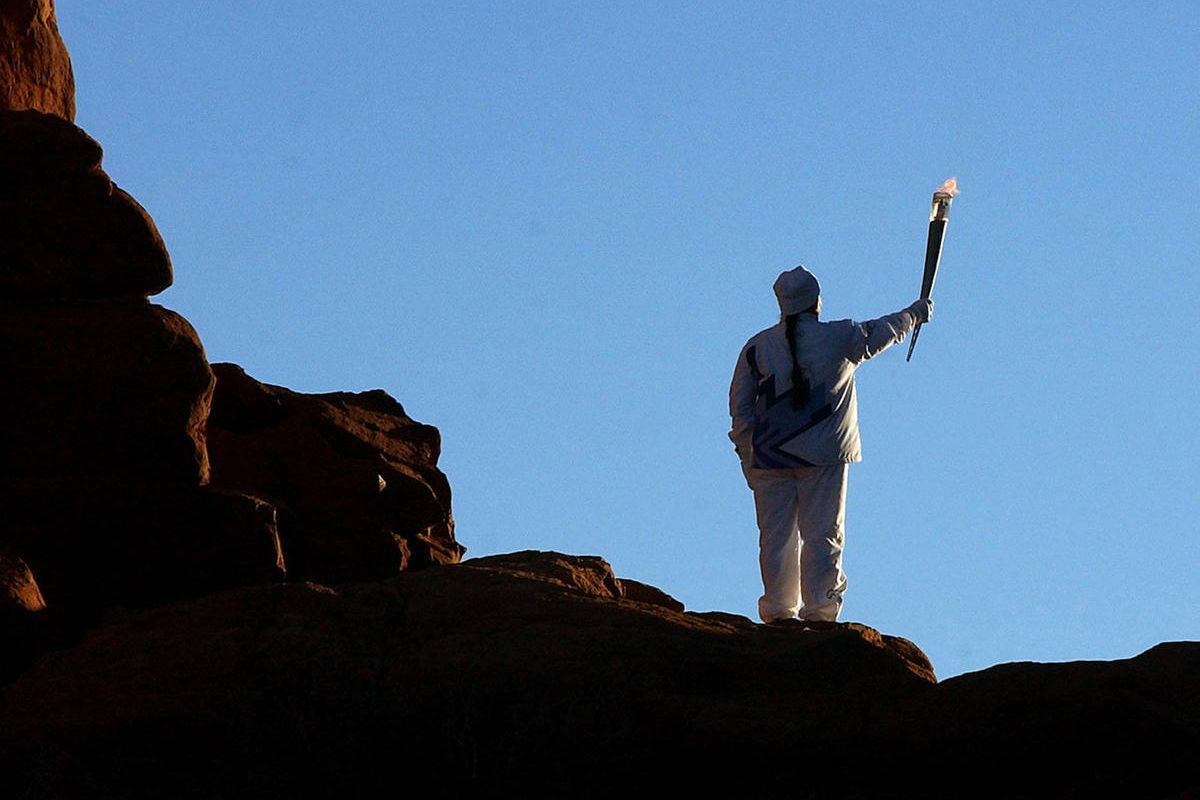 _FILE - An Olympic torchbearer presents the flame to the rising sun at the North Window arch in Utah's Arches National Park Monday, Feb. 3, 2002._