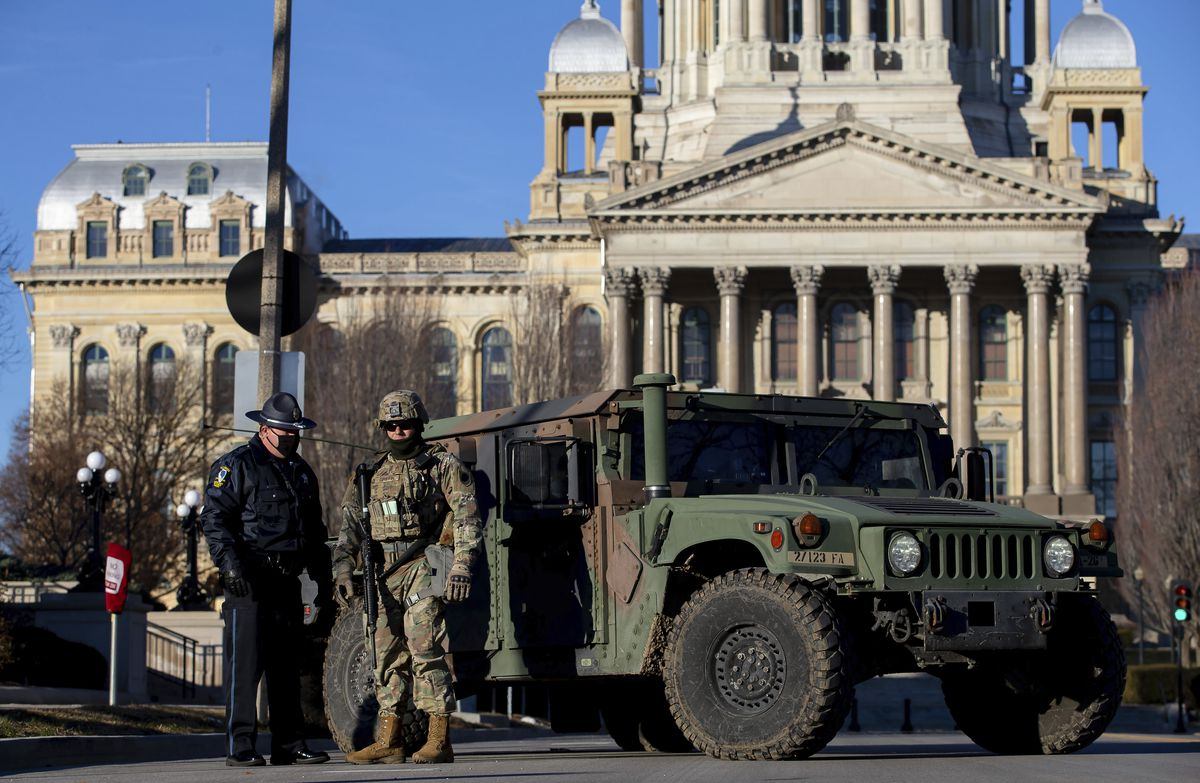 Members of the Illinois National Guard and the Capitol Police get setup in front of a road closure at the Illinois State Capitol earlier this month.