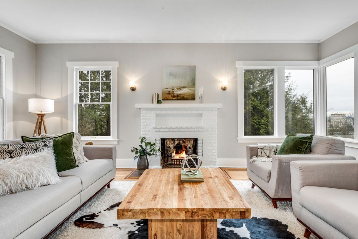 A living room has gray couches, a wooden coffee table, and a white fireplace.