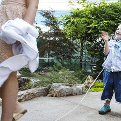 Dash Johnson, 4, right, a patient at Primary Children's Hospital, gets excited after throwing money into a pond during the reopening of the Angel Garden at the hospital in Salt Lake City on Monday, Aug. 1, 2016. The redesigned garden includes more than 1,000 new plants and trees, as well as legacy monuments, including the Butterfly Angel statue, a commissioned 5-foot bronze. Dash's family spearheaded renewal project.