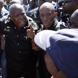 Firebrand politician Julius Malema, left, argues with police officers, at Lonmin Platinum Mine near Rustenburg, South Africa, Monday, Sept. 17, 2012. London-registered Lonmin PLC announced it is halting construction of a new shaft, putting 1,200 people out of work, as the bloody and bitter strike at its beleaguered South African platinum mine dragged on its fifth week. The strikes that have halted work at seven gold and platinum mines have spread to the chrome sector, according to the official South African Press Association. Meanwhile, police blocked rabblerousing politician Julius Malema from addressing some 3,000 strikers gathered at a stadium at the Lonmin mine at Marikana, northwest of Johannesburg.