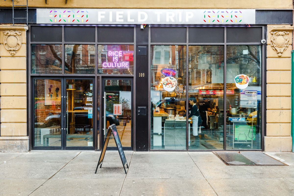 """A purple neon sign reads """"rice is culture,"""" behind the glass windows to FieldTrip in Harlem"""