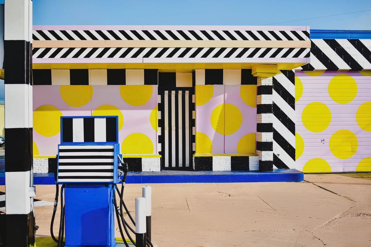 Gas station building painted with black and white stripes and yellow and pink dots.