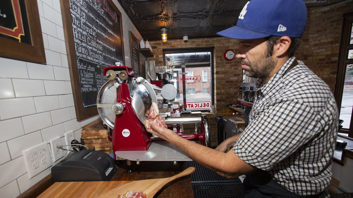 A man in a blue baseball hat cuts thin slices of cured meat on a red flywheel slicer.