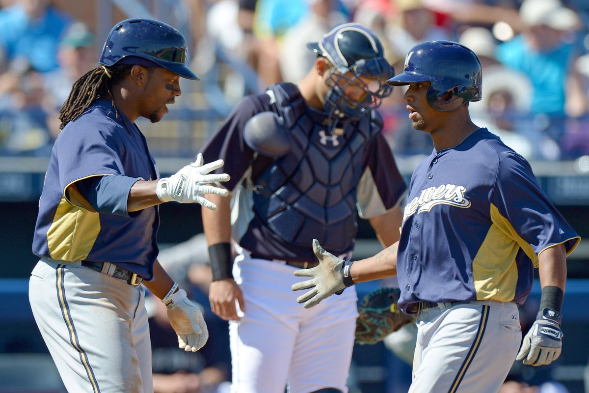 Khris Davis (R) is greeted at home plate after hitting a home run