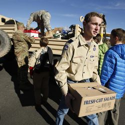 Boy Scout Alex Eyring, of Bountiful, unloads supplies after Santa Flight volunteers landed with Christmas gifts for students at Hurricane Elementary School in Hurricane on Wednesday, Dec. 7, 2016.