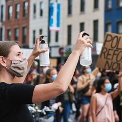Hand sanitizer is offered by a supporter for the marchers on Flatbush Avenue in Brooklyn on June 2, 2020.