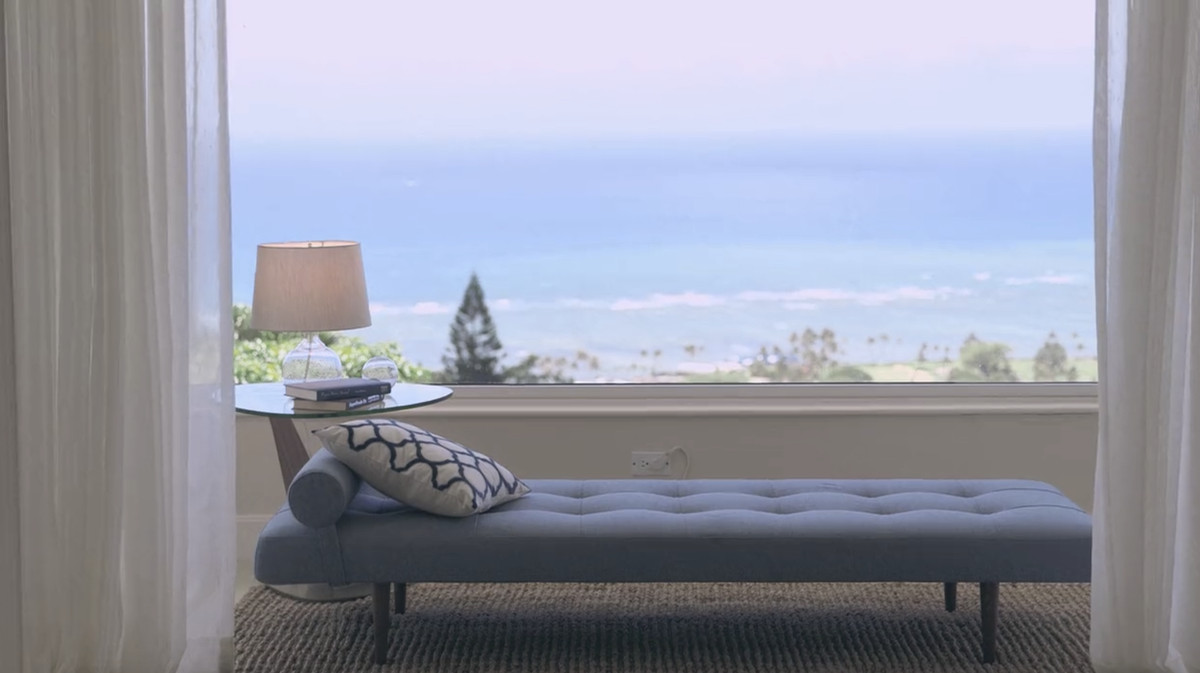 A grey lounge chair on a tan area rug is in the foreground. The lounge chair is next to a window with thin white curtains. The view from the window is a body of water.