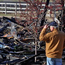 Area residents survey the wreckage Thursday, April 12, 2012 after a fire Wednesday evening destroyed Black Tie Stable and killed ten horses just West of Fox Lake in McHenry County, Ill.