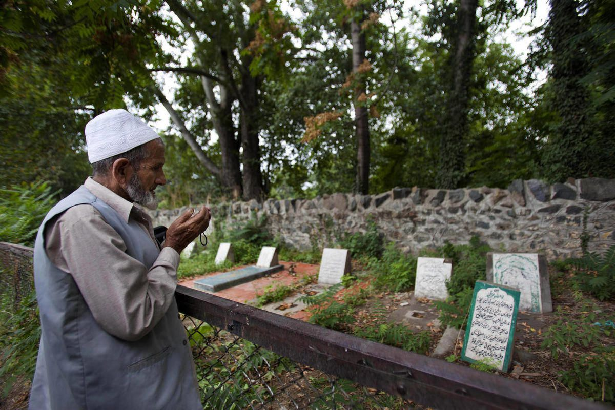 A Kashmiri Muslim prays near an unmarked grave, right foreground, inside a martyrs graveyard in Srinagar, India, Wednesday, Sept. 5, 2012. The government of Kashmir has rejected wide-scale DNA testing of bodies in thousands of unmarked graves despite plea