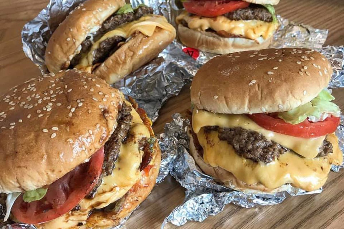 Four double cheeseburgers with lettuce, tomato, and onion