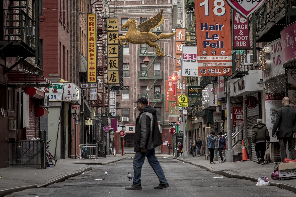 Manhattan's Chinatown with a man in the middle of the street.