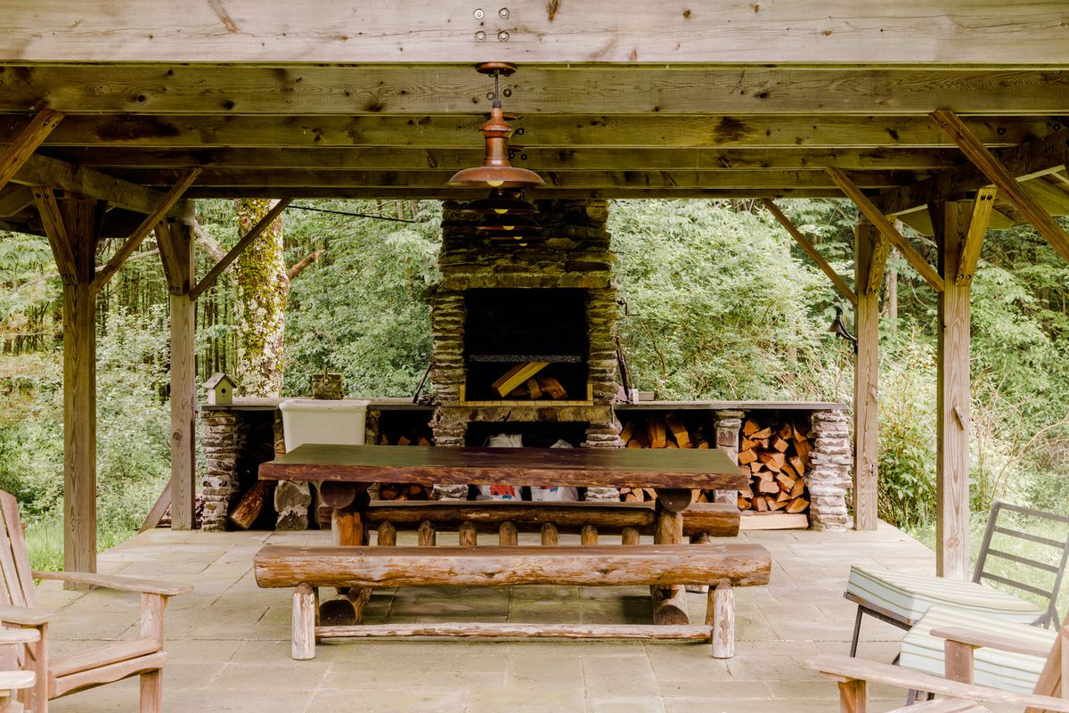 Trees surround an outdoor fireplace inside of a outdoor structure which does not have walls but has a roof and is supported by beams
