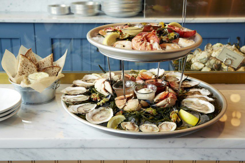 A two-level seafood tower, full of oysters, jumbo shrimp, and more, sits on a white marble counter in a restaurant. A bread basket is visible nearby.