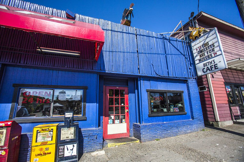 The exterior of Beth's Cafe with a red door and awning surrounded by painted blue walls.