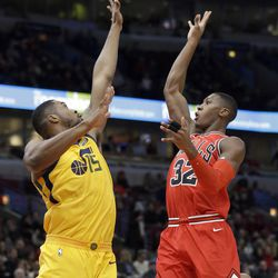 Chicago Bulls guard Kris Dunn, right, shoots over Utah Jazz forward/center Derrick Favors during the first half of an NBA basketball game Wednesday, Dec. 13, 2017, in Chicago. (AP Photo/Nam Y. Huh)