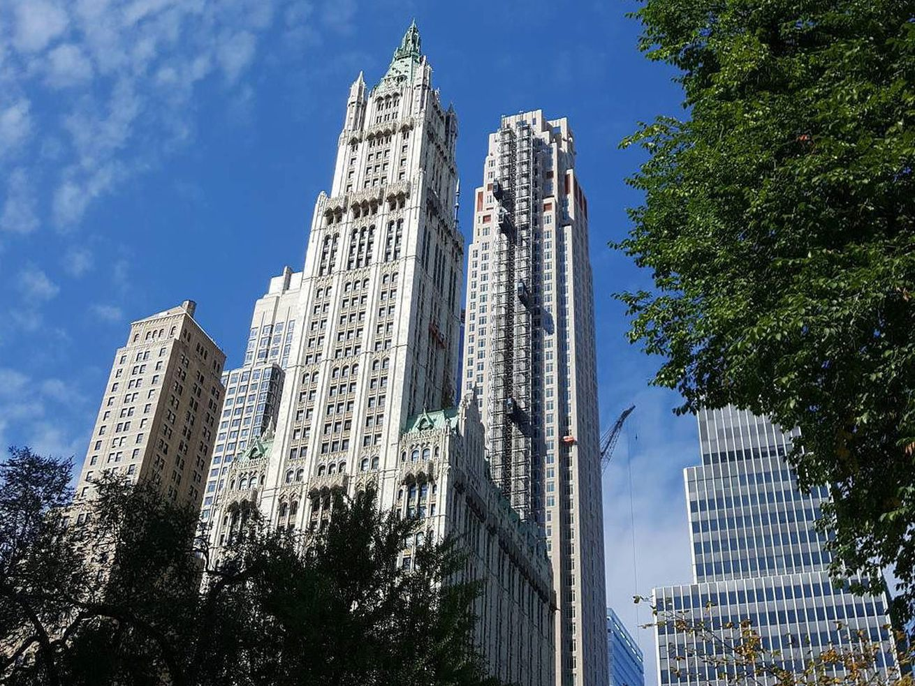 A high rise in Manhattan at 30 Park Place, with blue sky in the background and trees framing the photo.