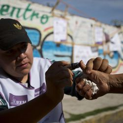 An election worker marks a man's thumb with ink after he cast his vote for governor at a polling station in Chicoloapan de Juarez, Mexico state, Sunday, June 4, 2017. Voters in Mexico's most populous state on Sunday could hand the ruling party a much-needed boost ahead of next year's presidential elections or a potentially devastating blow by throwing off its uninterrupted 88-year local rule.