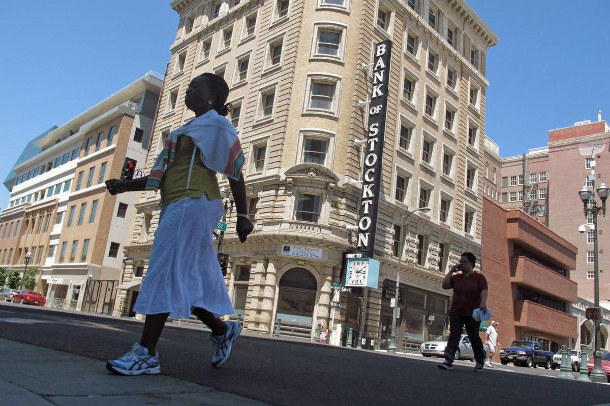 Pedestrians cross a street near the Bank of Stockton on Wednesday, June 27, 2012, in Stockton, Calif. When Stockton becomes the largest U.S. city ever to file for bankruptcy, it will strike a hard blow to residents, especially city employees and retirees