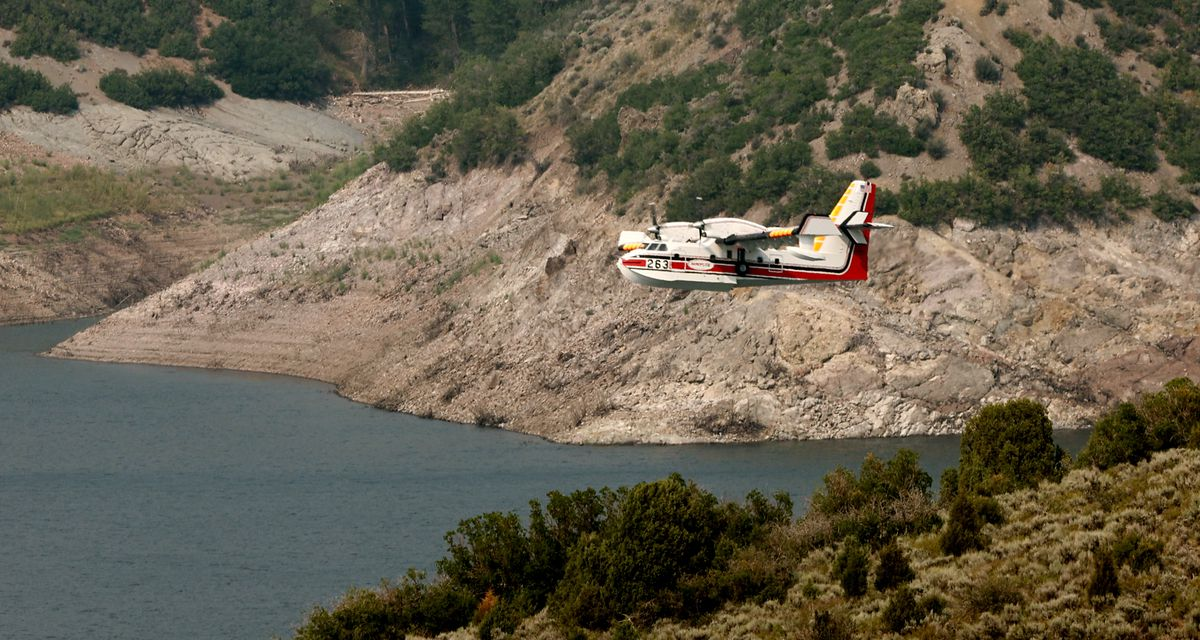 A water tanker lifts up after scooping water from the Jordanelle Reservoir as crews continue fighting the Parley's Canyon Fire near Park City on Sunday, Aug. 15, 2021.
