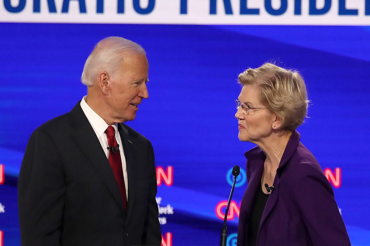 Biden and Warren chatting on the stage of the October Democratic debate.