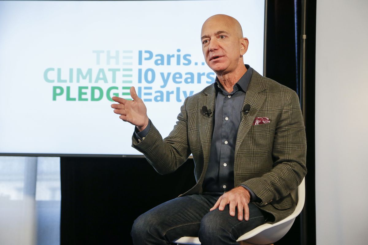 """Jeff Bezos onstage speaking in front of a screen that reads """"The climate pledge. Paris ... 10 years early."""""""