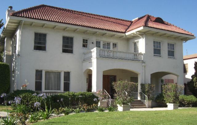 The exterior of the Wilfandel Club in Los Angeles. The facade is white with a brown roof. There is a yard in front of the building.