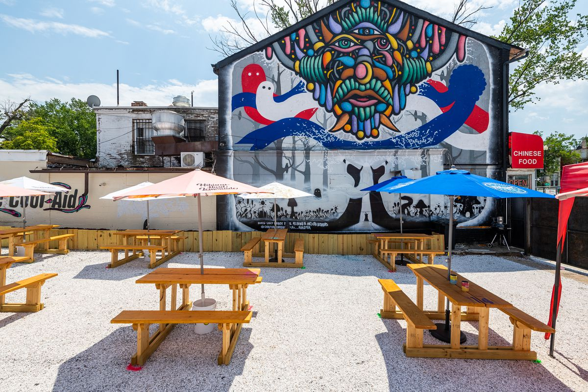 A trippy mural overlooks picnic tables at Electric Cool-Aid