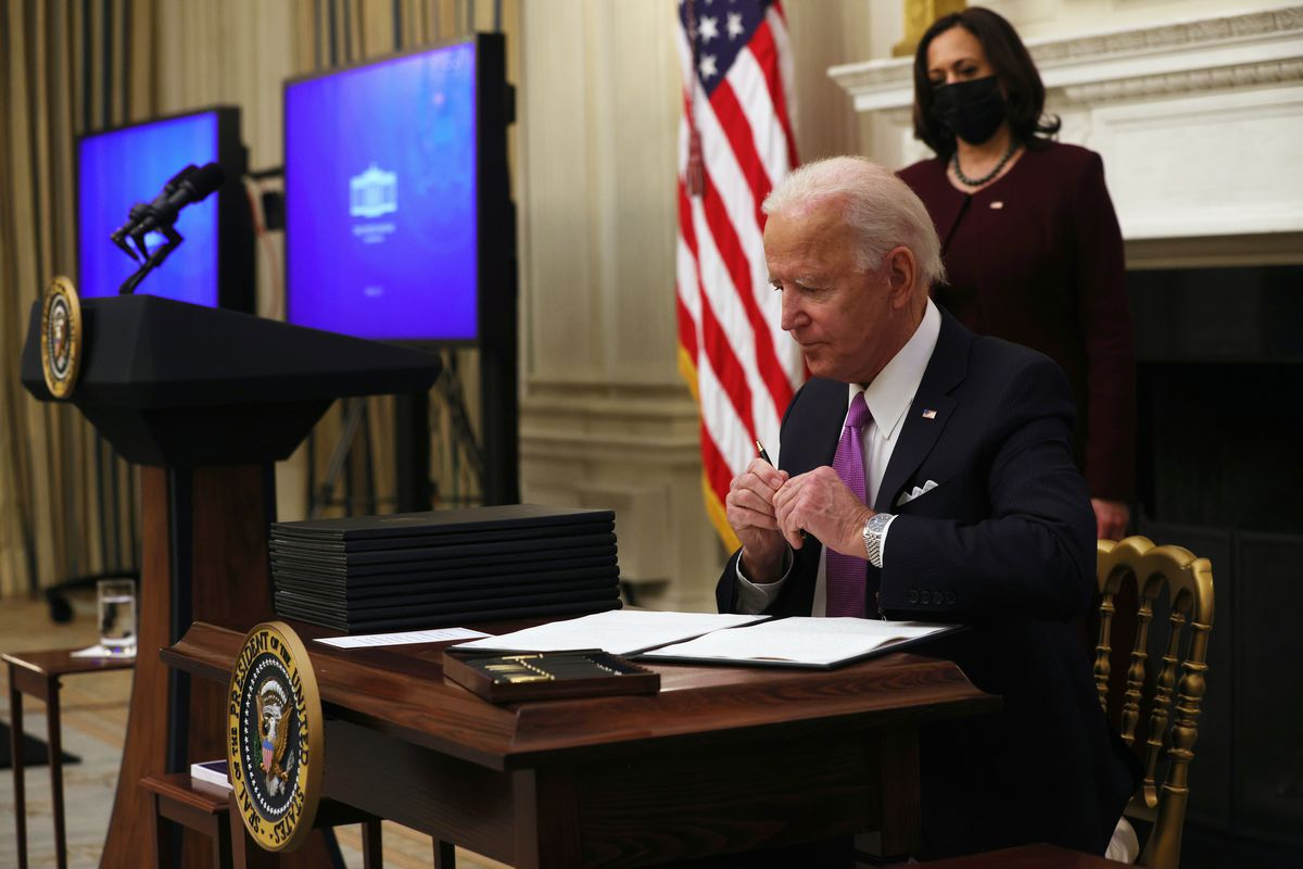 President Biden sits at a table signing documents with Vice President Kamala Harris standing behind him looking on.