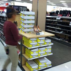 A staffer restocks the shoe section.