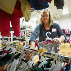 Volunteer Vicky Norton-Strong stocks clothing as the 19th annual Candy Cane Corner holiday store prepares to open in the old Granite High School pool building in South Salt Lake on Monday, Nov. 30, 2015.